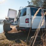 Junger Mann mit umgebautem Camper-Van am See